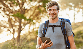 Image of man hiking with tablet computer